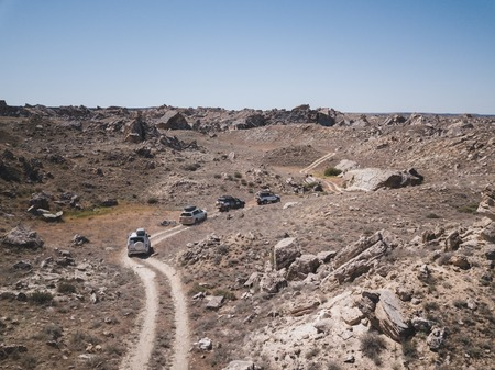 A convoy of cars rides the steppe among dust and stones. Aerial view in Kazahstan