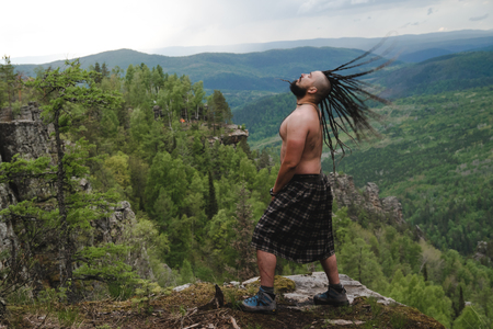 Celt on the edge of a cliff in the woods waving his head with dreadlocks Standard-Bild