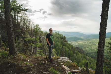 A young man in a black t-shirt stands on the edge of a cliff in the woods in the mountains