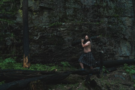 A man with soot on his face and in a Celtic skirt carries a charred log in the woods near the rock
