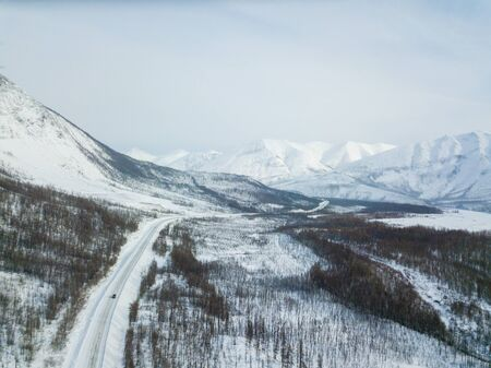 Winter road along the Kolyma highway among the mountains in Yakutia Standard-Bild