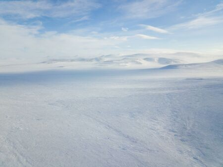 The cars rides on the snow-covered tundra ice in the far north. Aerial photography