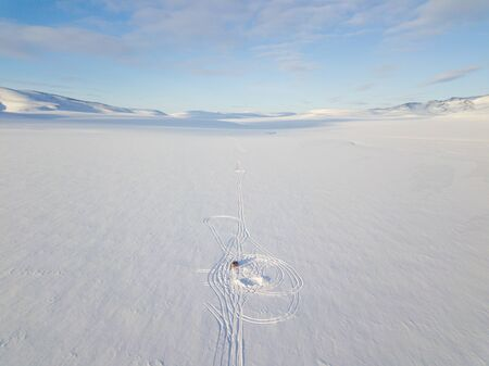 Road leading to nowhere. Aerial photography of a single rut among the snowy desert and mountains