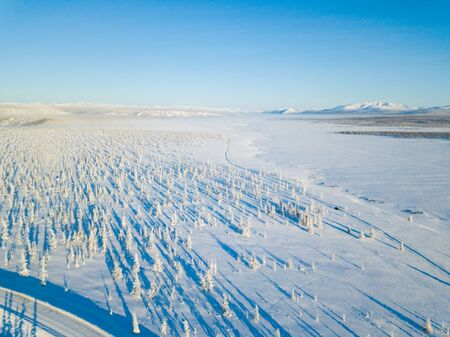 Winter road in the far north in Russia in Chukotka. Aerial photography with a forest view during sunset