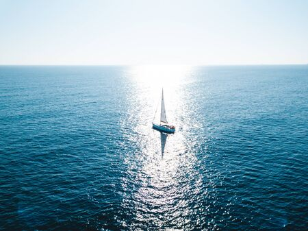 Silhouette of a yacht under sail opposite the reflection of the sun from the water
