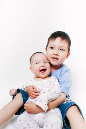 Portrait of Asian siblings. Elder brother hugging his little sister. Cute children. Family relations. White background. Surprised baby.