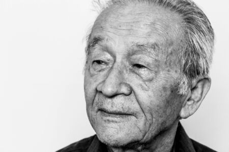 Closeup of elderly senior Asian man. Looking aside. Thinking about passed years. Black and white photo. 免版税图像