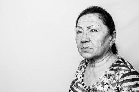 Portrait of elderly senior woman, black and white photo. Thinking about passed years. Loneliness, solitude.