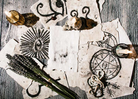 Old manuscripts with occult symbols, candles, lavender. Stock Photo