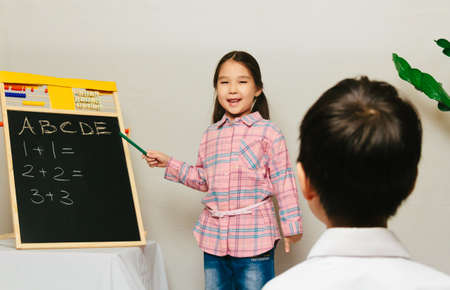 Little girl teaching a boy. Home education in Central Asia, lesson for kids Foto de archivo