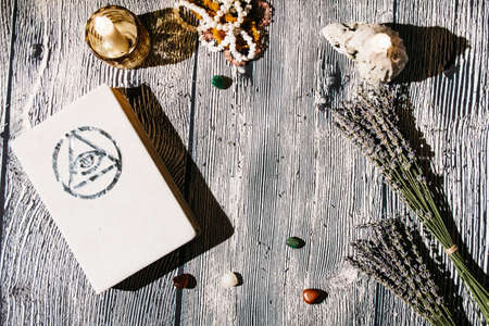 White magic book laying on the table with old manuscripts with occult symbols, candles, lavender. Concept of fortune telling, ritual, altar, spiritism, secret knowledge