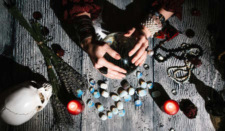 Fortuneteller's hands with stone runes, top view. Prediction of the future. Mystic interior. Occult symbols, rosaries, candles, dry lavender