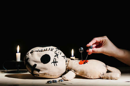 Woman's hand stabbing with a pin a voodoo doll during occult magic ritual on a black background with candles