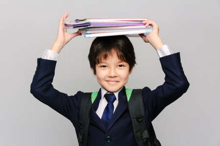 Close-up portrait of an Asian schoolboy holding his textbooks on his head and smiling Stockfoto