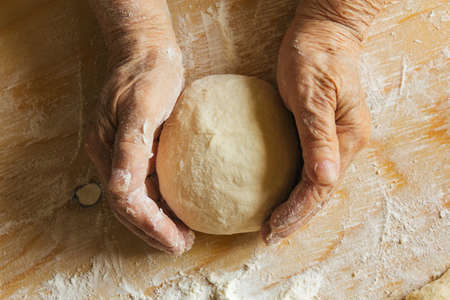 Cooking at home, old woman's hands kneading dough