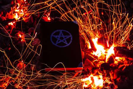 Black magic book. Beautiful occult ritual. Power of fire. Spitirual mood.
