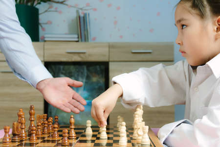 Family moments, little cute Asian girl playing chess with her father