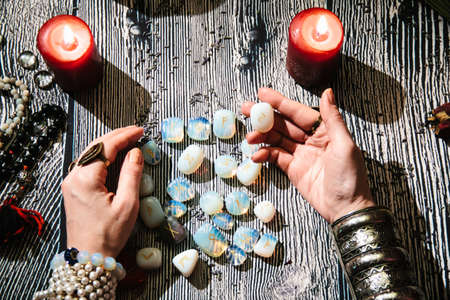 Fortuneteller's hands with stone runes, top view. Prediction of the future. Mystic interior. Occult symbols, rosaries, candles, dry lavender, skull