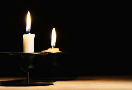 Beautiful black background with two lit candles