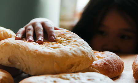 Cooking at home, little girl wants to taste fresh grandmother's bread