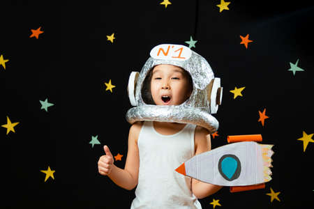 Portrait of a cute little Aisan girl, space at home, dreaming and playing astronaut. Funny family moments