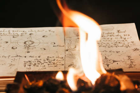 Occult white magic ritual of fire using grimoire, old book, candles