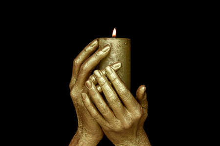 Lit gold candle in golden hands on black background. Occult ritual symbol of wealth and well-being. Banque d'images