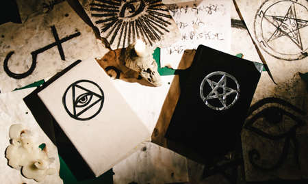 Occult grimoire, magic books laying on table with occult symbols, candles, pentagrams, fortune telling, ritual, altar, spiritism, secret knowledge, scull