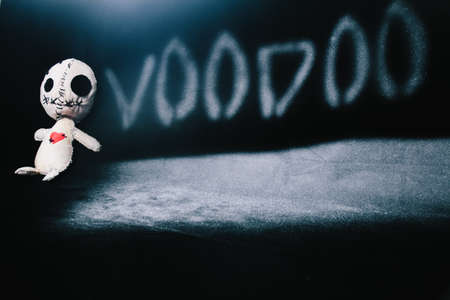 Voodoo magic ritual doll laying a black background