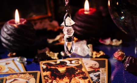 Beautiful crystal pendulum in a fortune teller's room. Tarot cards, occult symbol Foto de archivo