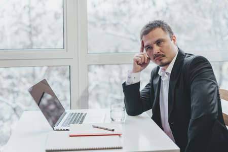 Asian successful businessman sitting at the table with laptop. Panoramic window background. Thinking pose, consideration