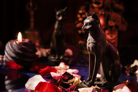 Mystical table with occult attributes. Stone rosaries, candles, ancient Egypt figurines of cats
