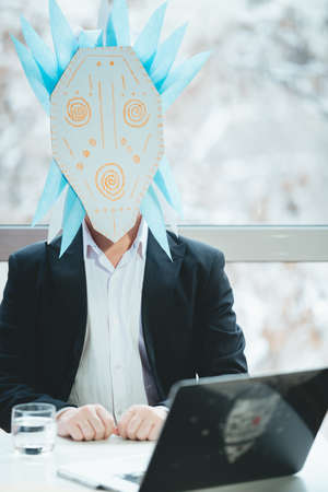 Asian businessman with tambourine in shamanic mask. Concept of attracting success, wishing good luck to business. Money increasing. Occult ritual, spiritism. Sitting at the table with laptop. 免版税图像