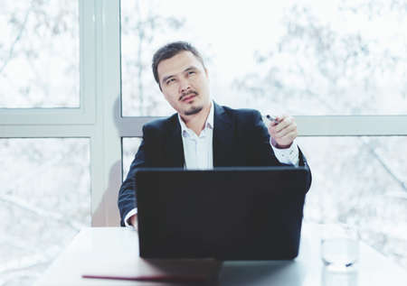 Asian successful businessman sitting at the table with laptop. Window background. Leader of meeting. Pointing finger.