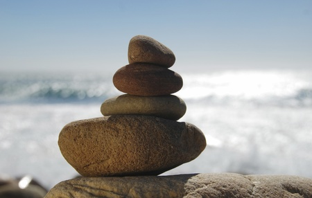 stones balancing on each other with sea behind photo
