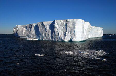 tabellare: tabular iceberg floating in the blue ocean