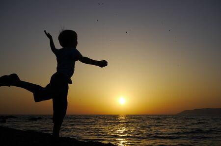 joyfully: young boy throws stones joyfully into sea