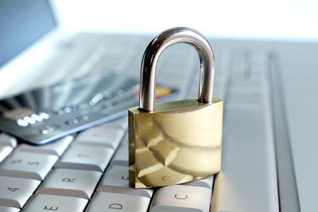 hacked: lock and credit card on a keyboard Stock Photo