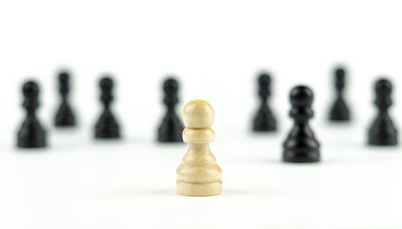 One white pawn standing along with black pawns
