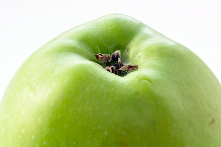 Upper part of a green apple with the stem.