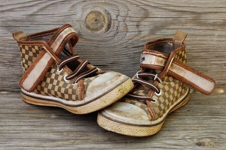 Old childrens shoes on the background of the wooden planks.