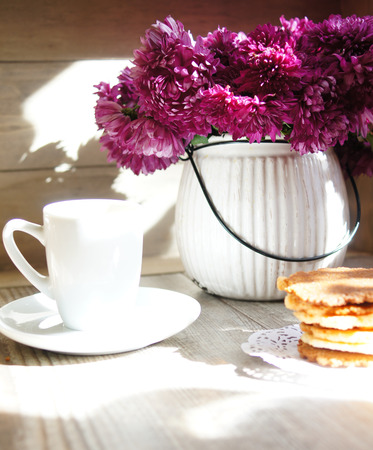 Cup of coffee,cookie and flower on the wooden table photo