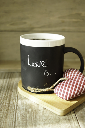 invigorate: A mug with Love is note and valentine decoratin on the wooden table