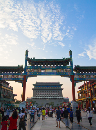 Pedestrian street Qianmen, traditional Chinese arch, walking people, blue sky, Beijing, China
