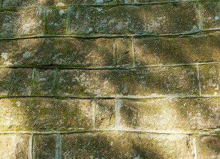 Old stone wall with sunbeams, oblong stones, sunny day, sun shine Фото со стока