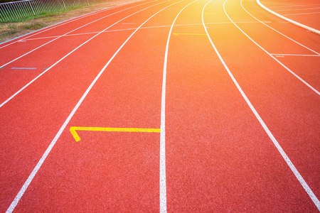White lines of stadium and texture of running racetrack red rubber racetracks in outdoor stadium are 8 track and green grass field