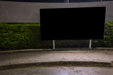 Blank billboard ready for new advertisement,lightbox mounted on the wall of store street in a city at night.