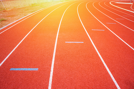 White lines of stadium and texture of running racetrack red rubber racetracks in outdoor stadium are 8 track and green grass field,empty athletics stadium with track,football field, soccer field. Stock Photo