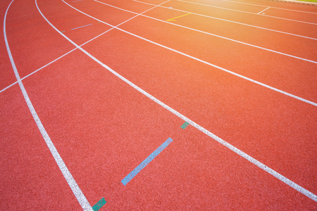 White lines of stadium and texture of running racetrack red rubber racetracks in outdoor stadium are 8 track and green grass field,empty athletics stadium with track.