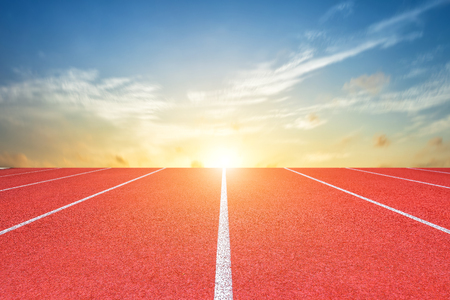 White lines of stadium and texture of running racetrack red rubber racetracks or Athlete track or running track with blue sky white cloud,sky sunset background.